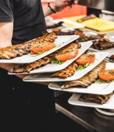 een ober met enkele borden ribbetjes